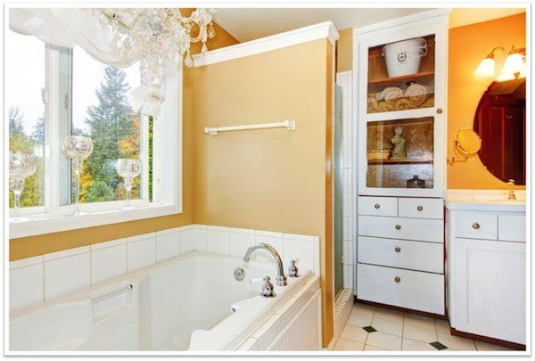 to the left is a window overseeing trees above a lovely bathtub and a shower and cabinets of to the right of it
